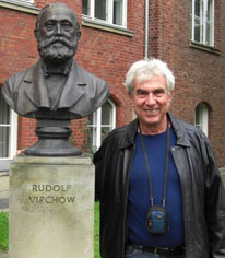 Michael Karin posing with a bust of Rudolf Virchow
