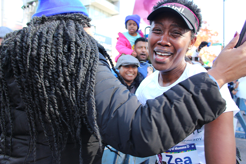 Zea McKenzie embraces family at the 8 Mile mark at the 2018 NYC Marathon