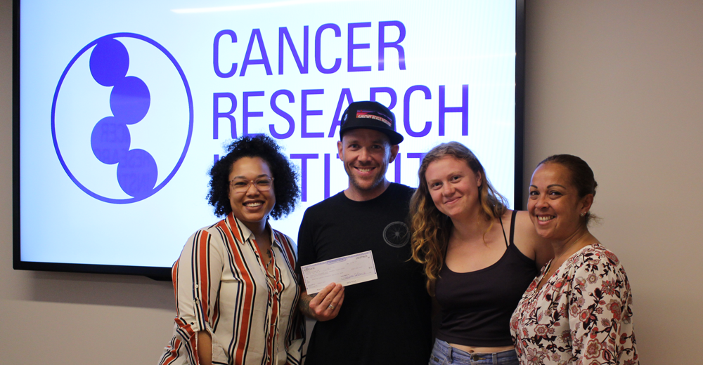 Brian delivers his check to the Cancer Research Institute