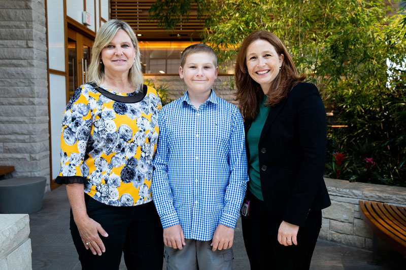 14-year-old Cole Malone (center) with his mom, Denise Malone (left), and one of his oncologists, DFCI's Dr. Susanne Baumeister (right). Photo by Adrianne Mathiowetz.