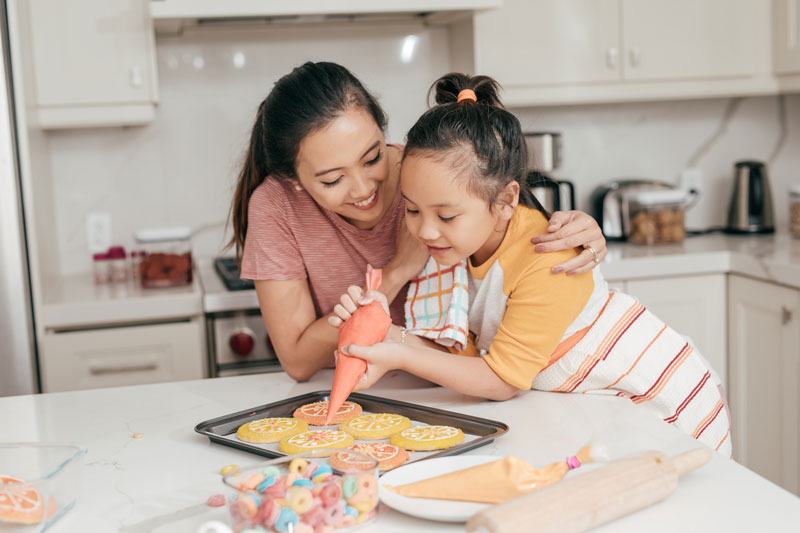 mother and child decorate cookies