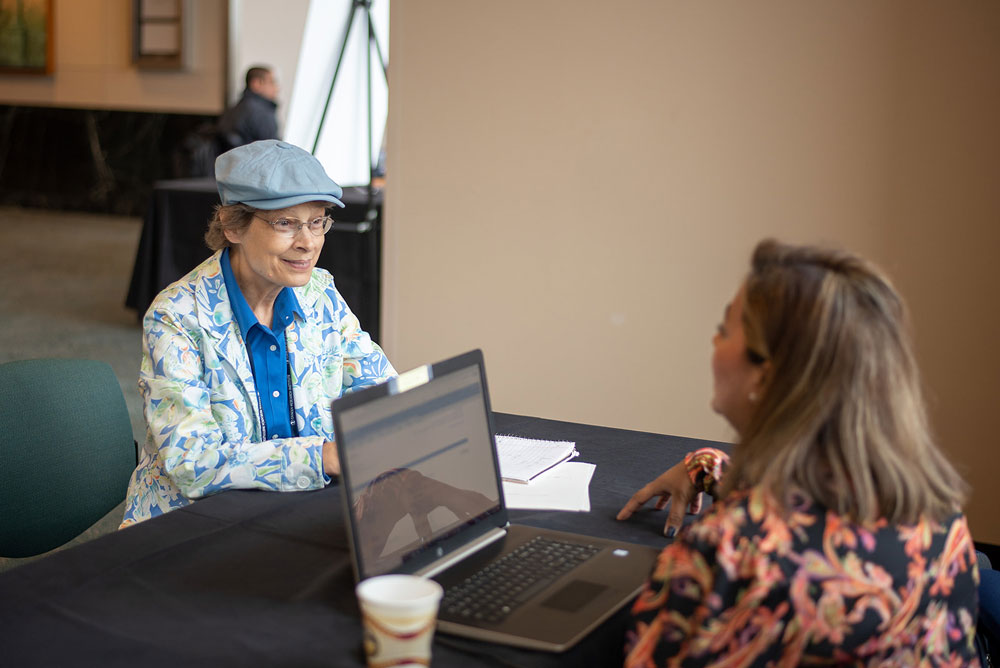 Summit attendee meets with a clinical trial navigator. Photo by Ranjani Groth.