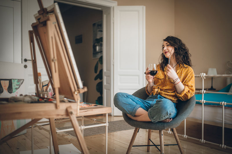 young woman drinks wine and paints