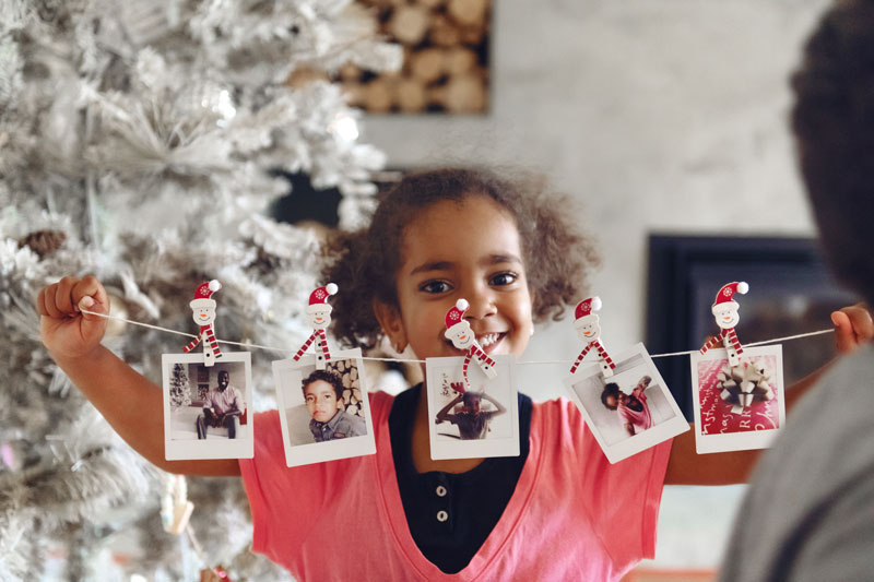 oung girl holding family photos to decorate tree